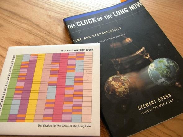 ブライアン・イーノさんのCD「JANUARY 07003」(左)とスチュアート・ブランドさんの著書「The Clock of the LONG NOW」